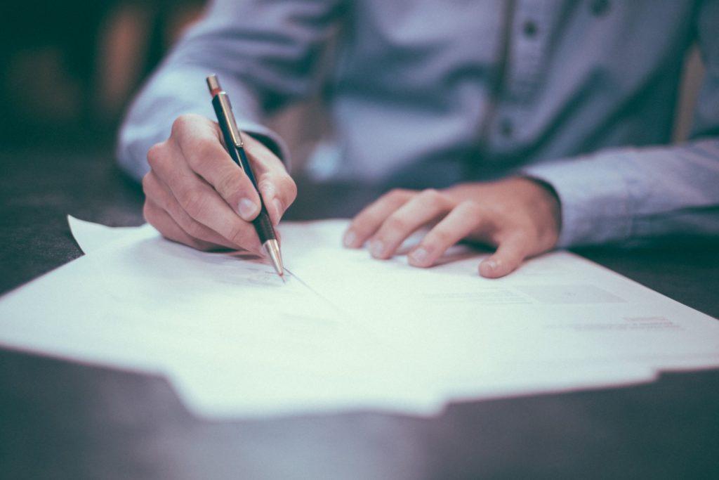 A businessman writing on paper. Photo source: Scott Graham via Unsplash