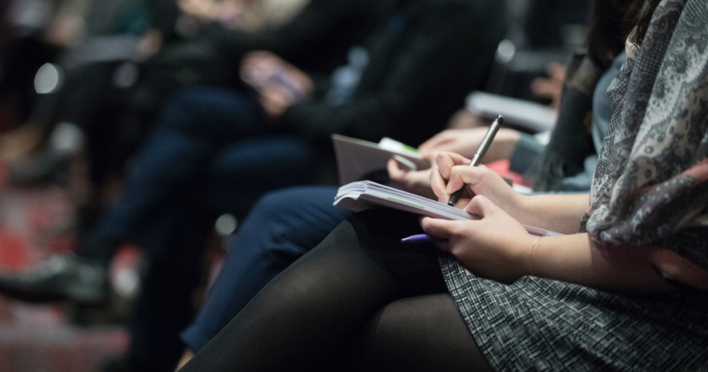 A photo of people taking notes during a business conference.