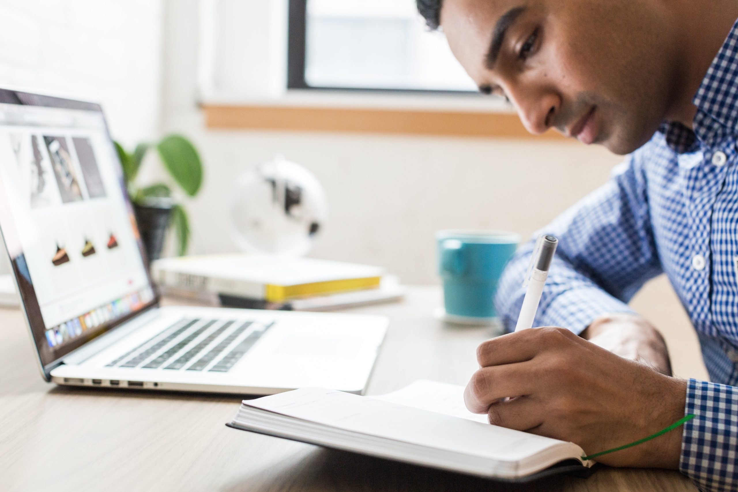 A businessman sitting at his computer, taking notes on the 10 Best Amazon Seller Blogs of 2020.