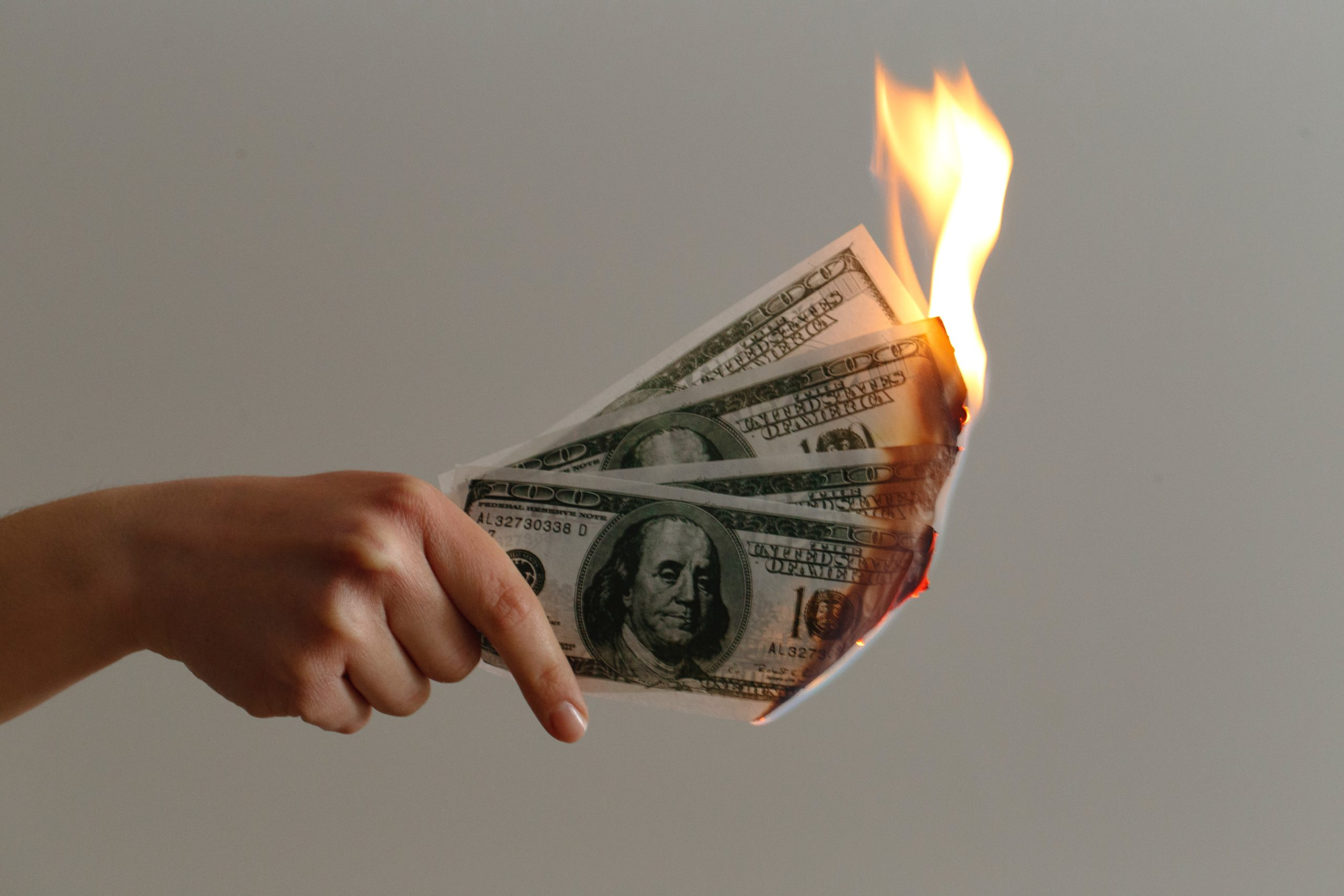 A photo of three $100 bills on fire, signifying the way that small businesses waste money.