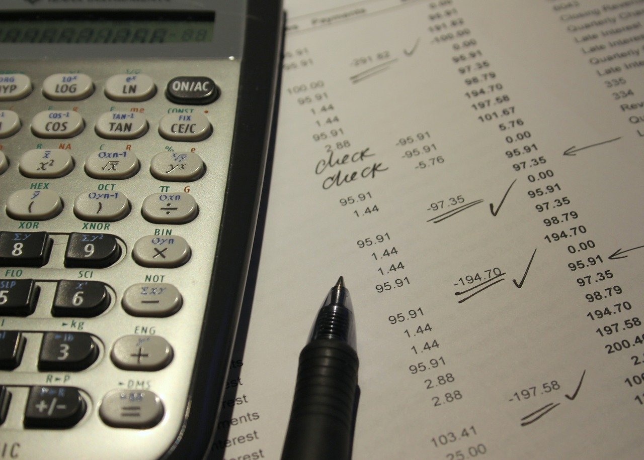 A calculator and sheet with expenses listed.