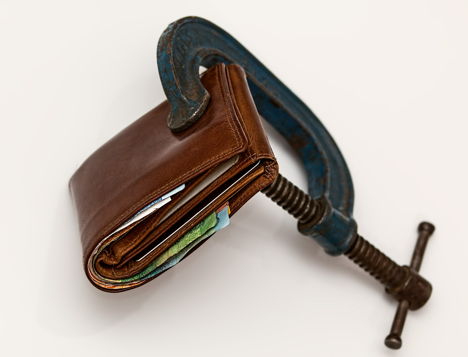 A wallet being squeezed by a mechanical device. The image is meant to depict the financial stress of the Cost of Goods Sold (COGS).