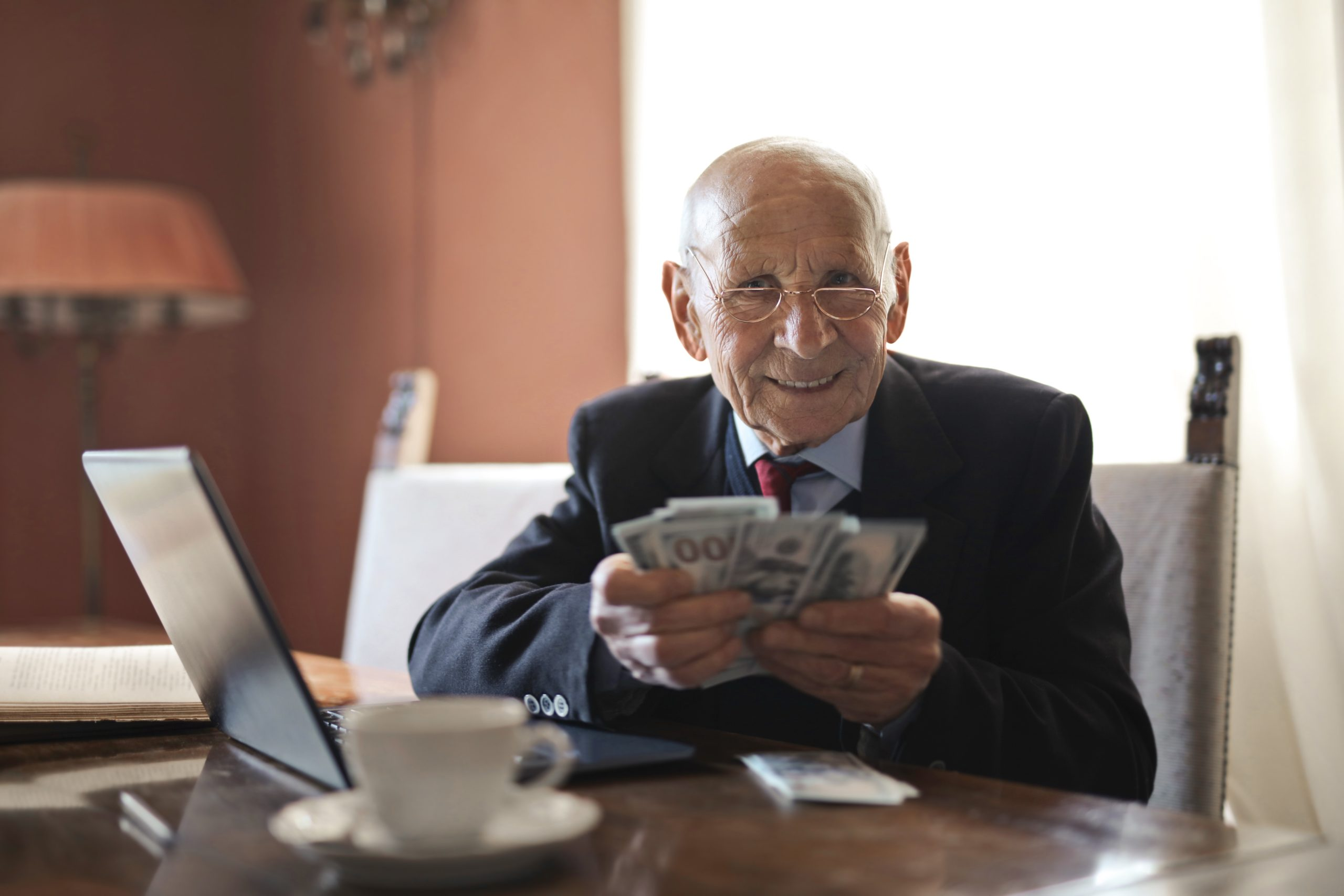 """A """"gross"""" looking old man holding a wad of cash."""