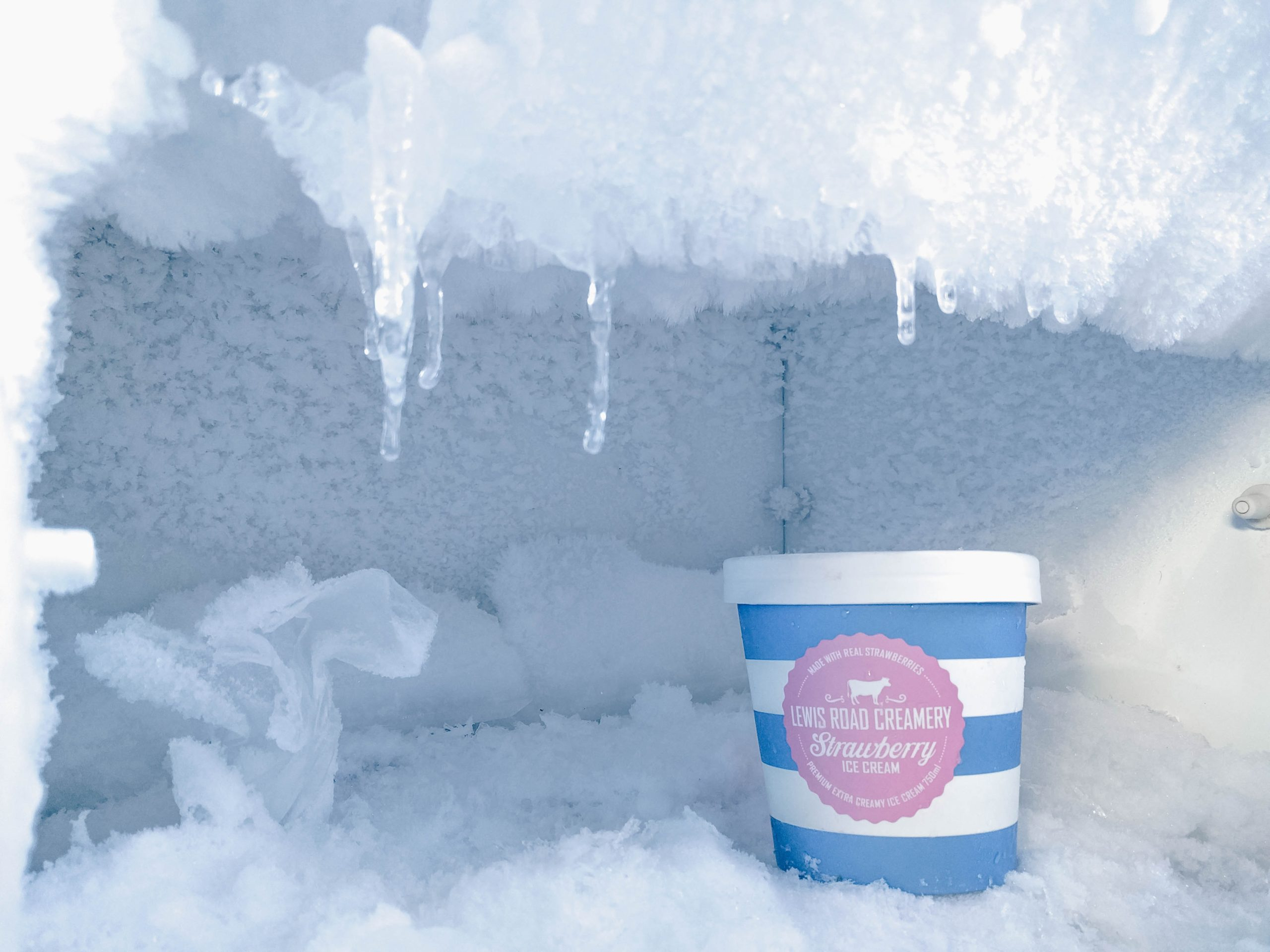 A tub of ice cream in a freezer.