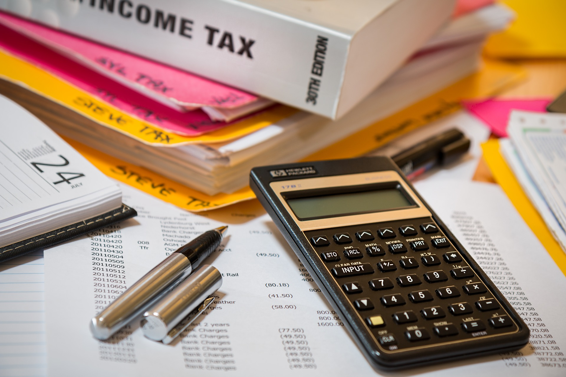 A desk with various accounting materials piled on top, including a calculator, a financial spreadsheet, and a book about income tax.