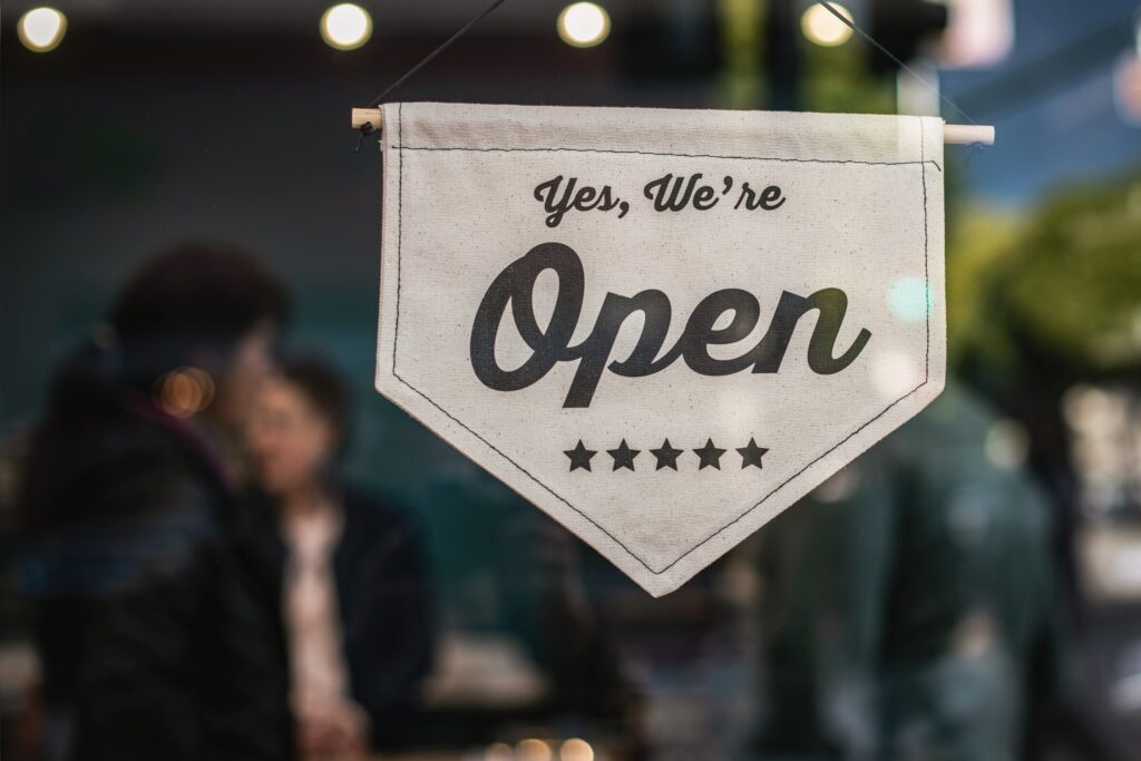 """A small business with a sign posted on the front door that reads, """"Yes, we're open."""""""