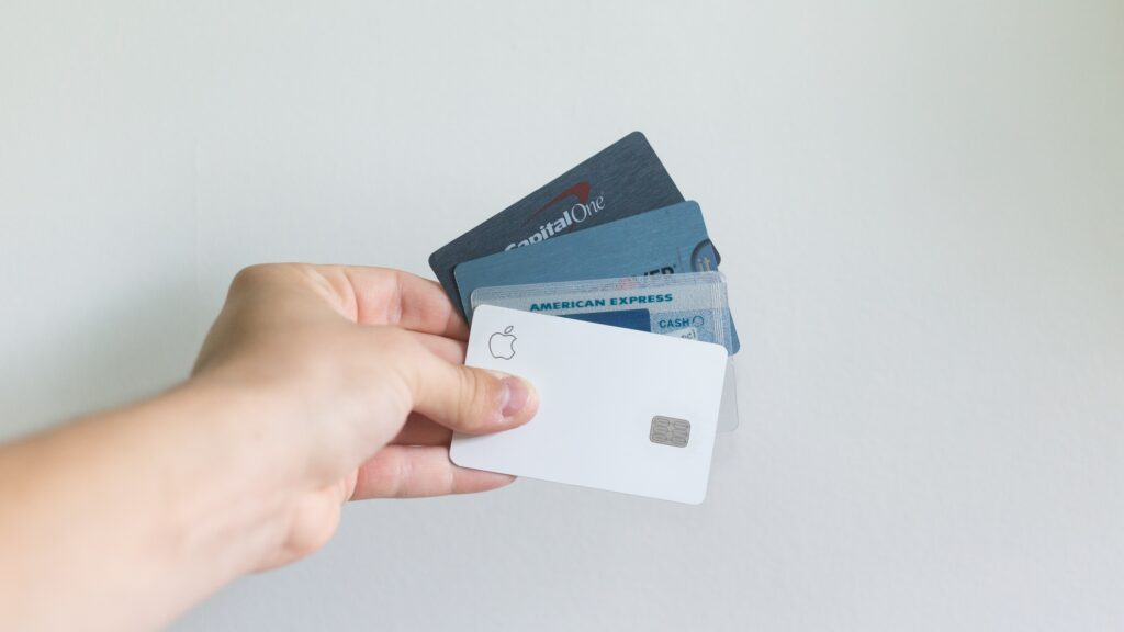 A person holding an assortment of U.S. credit cards.