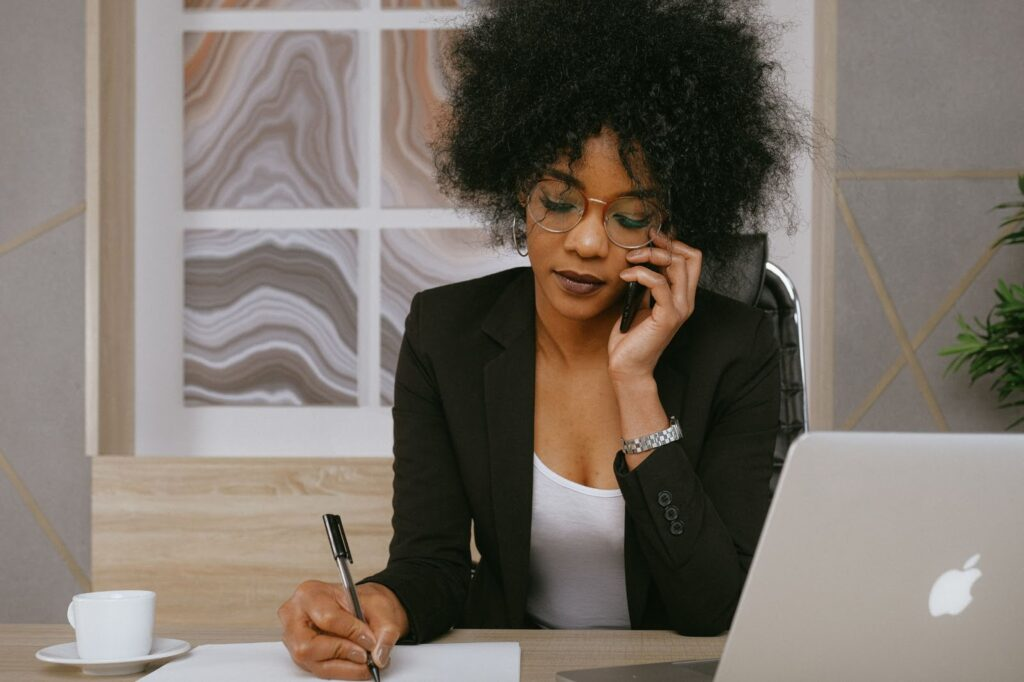 A businesswoman on the phone inquiring about professional bookkeeping services.